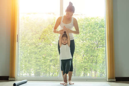 Foto de Asian mom practice yoga with a adorable daughter at home, try to teach young daughter to do yoga tree pose or vrksasana while exercise at home. - Imagen libre de derechos
