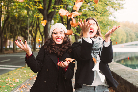 Funny girl friends throwing dry leaves in the city in autumn