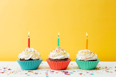 Photo pour Three colorful  birthday cupcakes with candles and confetti on a yellow background - image libre de droit