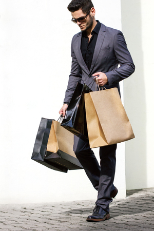 Photo for Handsome man in suit with shopping bag - Royalty Free Image