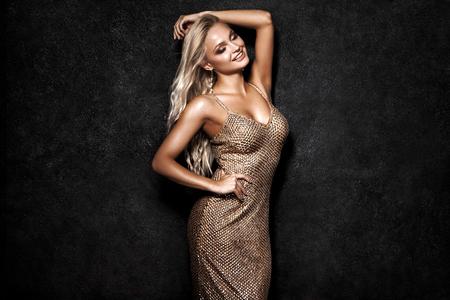 Foto de Beautiful sexy blonde woman on black background, party. - Imagen libre de derechos