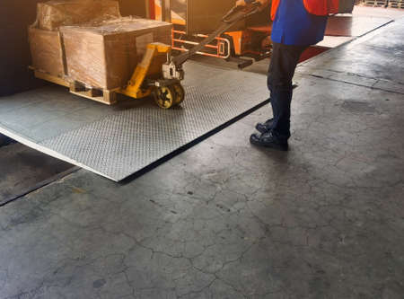 Photo for Worker driving forklift loading shipment carton boxes and goods on wooden pallet at loading dock from container truck to warehouse cargo storage in freight logistics and transportation industria - Royalty Free Image