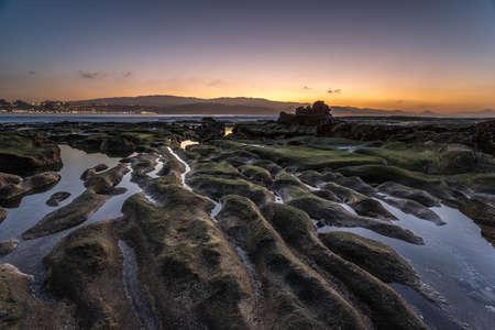 Beautiful colorful sunset landscape at El Confital beach, sky reflections on water, natural rock formation. La Isleta Peninsula, Gran Canaria, Spain