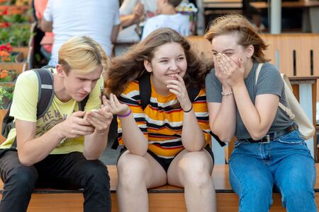 Photo for RIGA, LATVIA - JULY 26, 2018: Teenagers sit on the bench, talk and laugh. - Royalty Free Image