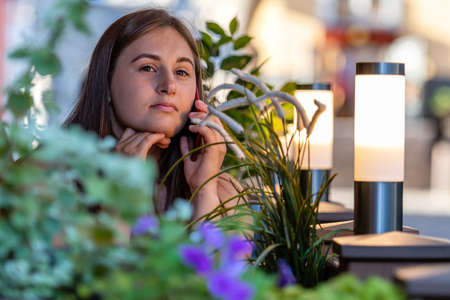 Photo for joyful young woman talking on cellphone while sitting at street cafe outdoors - Royalty Free Image