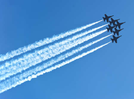 six jet planes with air trails in the deep blue sky