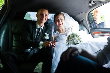 Foto de happy wedding couple sitting in limo - Imagen libre de derechos