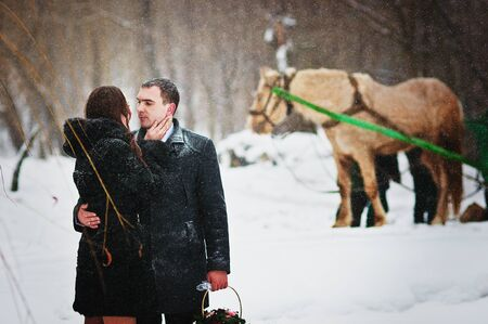 Young loved couple on winter snowly day