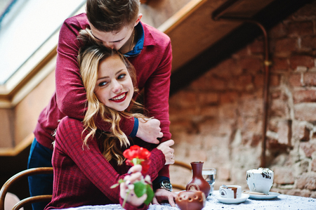 Photo pour Young beautiful stylish couple in a red dress in love story at the vintage cafe with big windows at the roof, boy gives flower as present for girlfriend - image libre de droit