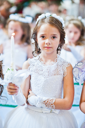 Photo for Portrait of cute little girl on white dress and wreath on first holy communion with burning candle at hands on church - Royalty Free Image