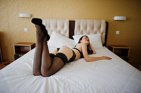 Hot young woman laying on a bed and posing in lingerie and high heels.