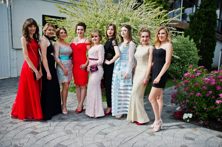 Photo pour Faulous young women graduates in chic evening gowns posing outside in the park. - image libre de droit