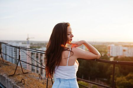 Photo pour Portrait of a gorgeous young woman in casual clothing admiring the sunset from the roof of a building. - image libre de droit