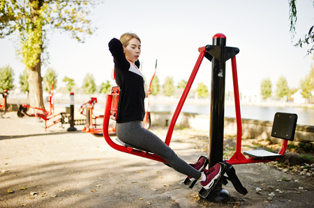 Young girl has the training and doing exercise outdoors on street simulators. Sport, fitness, street workout concept.