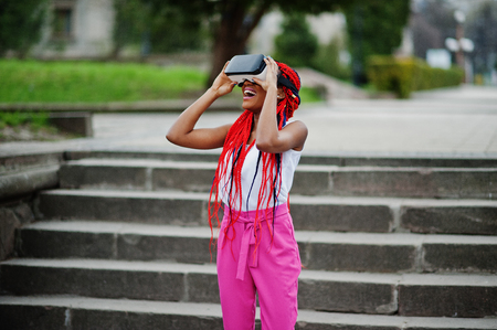 Fashionable african american business woman at pink pants and red dreads with virtual reality glasses outdoor.