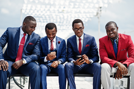 Group of four african american happy succesfull mans at suit. Rich black business mans sitting at chairs looking at mobile phones.