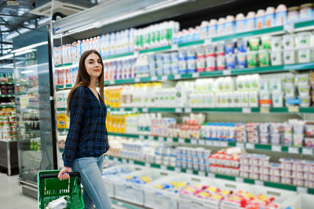 Shopping woman looking at the shelves in the supermarket.  Portrait of a young girl in a market store holding green shop basket and milk production.