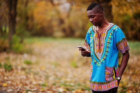 Foto de African man in africa traditional shirt on autumn park. - Imagen libre de derechos