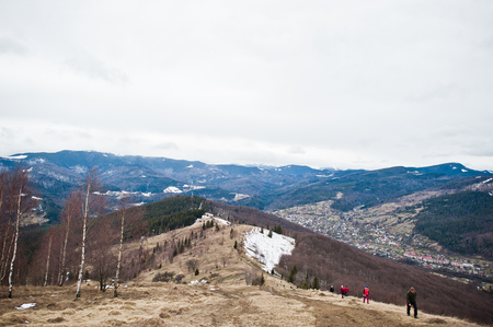 Tourists group hiking at snowy mountain valleys at Carpathian mountains. View of Ukrainian Carpathians and Yaremche from the top of Makovitsa.
