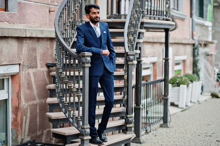 Photo pour Stylish beard indian man with bindi on forehead, wear on blue suit posed outdoor against iron stairs. - image libre de droit