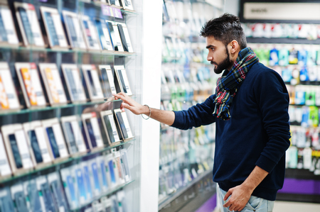 Photo pour Indian beard man customer buyer at mobile phone store choose his new smartphone. South asian peoples and technologies concept. Cellphone shop. - image libre de droit