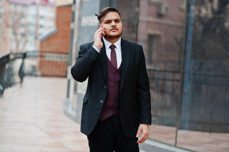 Photo pour Stylish indian businessman in formal wear standing against windows in business center and speaking on phone. - image libre de droit