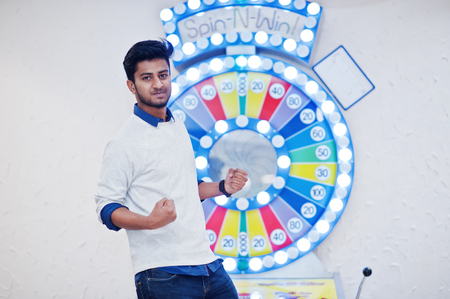 Photo pour I'm a millionaire! Very excited young asian man against fortune wheel win at lottery great prize. - image libre de droit