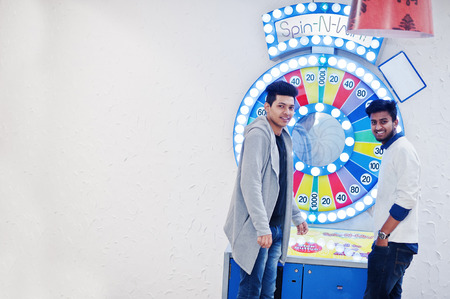Photo pour Two young asian guys play in fortune wheel to win at lottery big prize. - image libre de droit