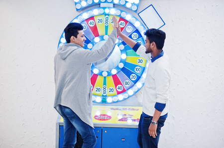 Photo pour We are millionaires! Very excited two young asian guys against fortune wheel win at lottery big prize. Give high five each other. - image libre de droit