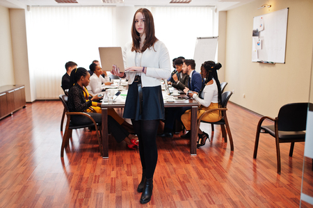 Face of handsome european business woman, holding laptop on the background of business peoples multiracial team meeting, sitting in office table.