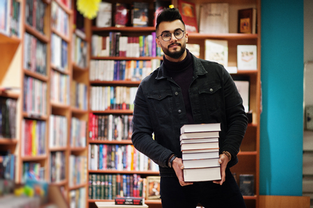 Photo for Tall smart arab student man, wear on black jeans jacket and eyeglasses, at library with stack of books. - Royalty Free Image