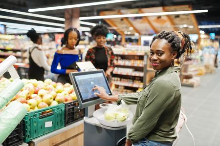 Foto für Group of african womans weighs apples in polyethylene bags at supermarket. - Lizenzfreies Bild