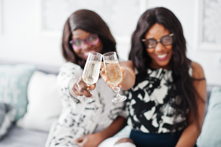 Photo pour Two african woman friends wear on eyeglasses posed indoor white room and drink champagne from glasses. - image libre de droit