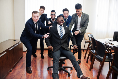 Photo for Six multiracial business mans standing at office and roll man on chair. Diverse group of male employees in formal wear having fun. - Royalty Free Image