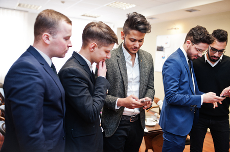 Photo pour Six multiracial business mans standing at office and use mobile phones. Diverse group of male employees in formal wear with cellphones. - image libre de droit