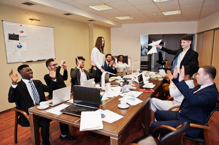 Photo pour Multiracial business team meeting around boardroom table, two team leaders throw paper up. - image libre de droit