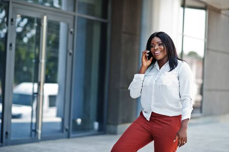 Formally dressed african american business woman in white blouse and red trousers with mobile phone. Successful dark skinned businesswoman.