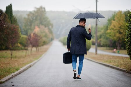 Foto de Fashionable tall arab beard man wear on black coat with umbrella and bag case posed at rain weather day. - Imagen libre de derechos