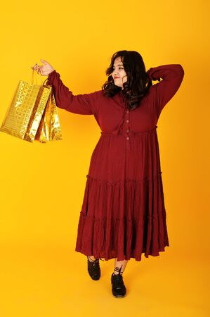 Photo for Attractive south asian woman in deep red gown dress posed at studio on yellow background with golden shopping bags. - Royalty Free Image