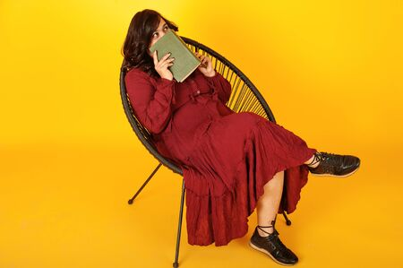 Photo for Attractive south asian woman in deep red gown dress posed at studio on yellow background sitting on chair with book. - Royalty Free Image