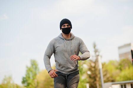 Photo for Portrait sports arabian man in black medical face mask run outdoor during coronavirus quarantine. - Royalty Free Image