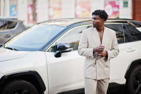 Photo pour Stylish afro man in beige old school suit against modern hybrid electro suv car. Fashionable young African male in casual jacket on bare torso. - image libre de droit