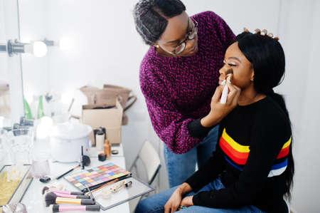 Foto de African American woman applying make-up by make-up artist at beauty saloon. - Imagen libre de derechos