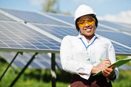 Photo for African american technician check the maintenance of the solar panels. Black woman engineer at solar station. - Royalty Free Image