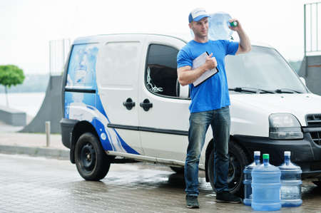 Photo for Delivery man with clipboard in front cargo van delivering bottles of water. - Royalty Free Image