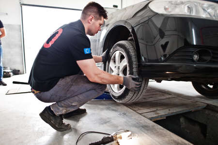 Car repair and maintenance theme. Mechanic in uniform working in auto service, checking tires.