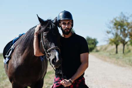 Photo for Arab tall beard man wear in black helmet with arabian horse. - Royalty Free Image