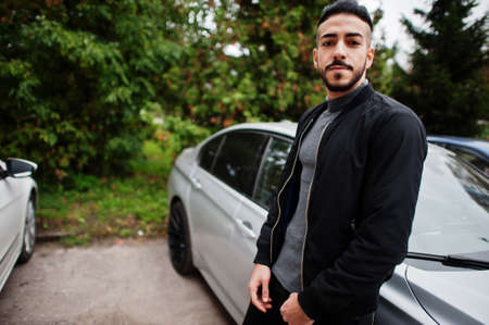 Photo pour Portrait of stylish arab beard man wear gray turtleneck and black jaket. Arabian model guy stand near his car. - image libre de droit