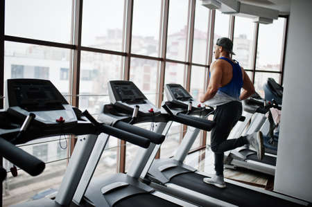 Photo for Fit and muscular arabian man running on treadmill in gym. - Royalty Free Image