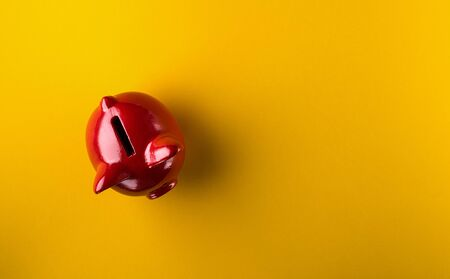 Photo pour Red piggy bank on yellow background - image libre de droit